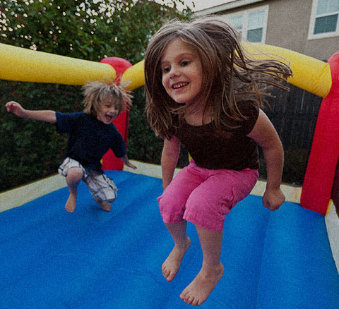 Young girl and boy enjoy a jumping in a bounce house