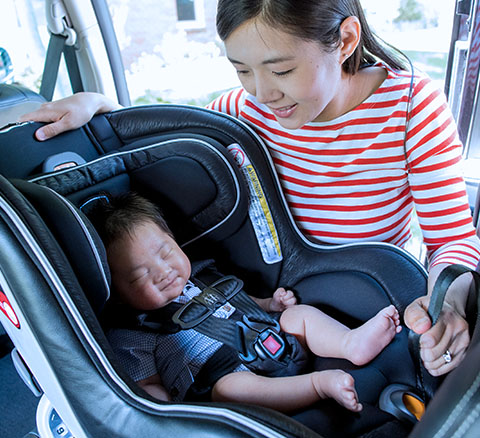 A parent fastens the straps to their childs car seat